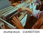 woman is choosing a vinyl... | Shutterstock . vector #1164837334