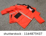 simple red work clothes stacked ... | Shutterstock . vector #1164875437