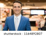 smiling businessman in a store   Shutterstock . vector #1164892807