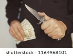 robber with knife in hand and... | Shutterstock . vector #1164968101