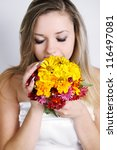 Beautiful woman smelling a bouquet of autumn flowers - stock photo