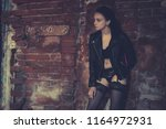 sexy model stands old brick... | Shutterstock . vector #1164972931
