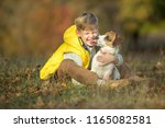child with dog in autumn  | Shutterstock . vector #1165082581