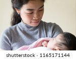 asian mother holding newborn... | Shutterstock . vector #1165171144
