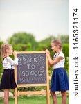 happy little schoolgirls with a ... | Shutterstock . vector #1165321174