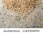 scattered raw rice on grey... | Shutterstock . vector #1165344094