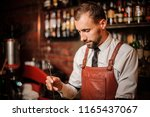 bartender in the white shirt... | Shutterstock . vector #1165437067