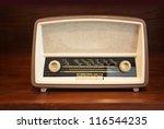 Old radio on wooden shelf - stock photo