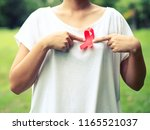 female hands holding red aids... | Shutterstock . vector #1165521037