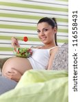 Cute pregnant woman sitting on couch in living room and eating salad - stock photo
