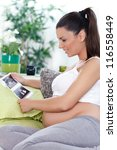pregnant woman sitting on a sofa looking at her unborn baby's ultrasound scan. - stock photo