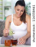Beautiful pregnant woman relaxing with cup of tea - stock photo