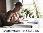 Small photo of Work goes smoother with right music in ears. Attractive serious-looking woman in glasses with fair hair in beige pullover, making notes and reading book while sitting near window, using laptop