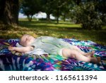 a cute baby napping outside on... | Shutterstock . vector #1165611394