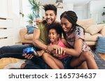 smiling family sitting on the... | Shutterstock . vector #1165734637