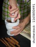 female hands grind the cinnamon ... | Shutterstock . vector #1165850491
