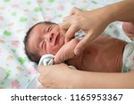 mother changing baby clothes ... | Shutterstock . vector #1165953367