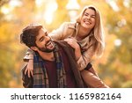 young smiling couple enjoying... | Shutterstock . vector #1165982164
