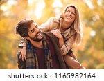 young smiling couple enjoying... | Shutterstock . vector #1165982164