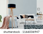 lamp next to white sofa with... | Shutterstock . vector #1166036947