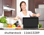 Woman showing laptop cooking in kitchen. Focus on screen with copy space. Excited mixed race asian caucasian young woman in her kitchen. - stock photo