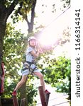 young girl climbs the rope park | Shutterstock . vector #1166314141