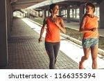 two female runners jogging... | Shutterstock . vector #1166355394