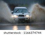 driving through floodwater... | Shutterstock . vector #1166374744