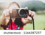 women holding vintage camera... | Shutterstock . vector #1166387257