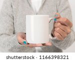 Hand holding white ceramic coffee cup. mockup for creative design branding.