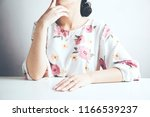young woman sitting at table | Shutterstock . vector #1166539237