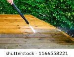 cleaning terrace with a power... | Shutterstock . vector #1166558221