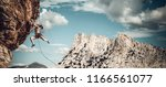 female climber struggeling up a ... | Shutterstock . vector #1166561077