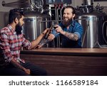 Small photo of Two bearded interracial friends drink craft beer in a brewery. Tattooed hipster worker male in an apron drinks beer with his friend in the brewery factory.