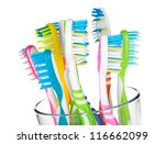 Colorful toothbrushes in glass. Closeup. Isolated on white background - stock photo