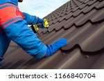 Small photo of Man worker uses a power drill to attach a cap metal roofing job with screws.