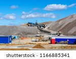 Small photo of dumps of mined rock with belt conveyors, stackers and working bulldozer, general view