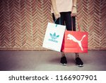 Small photo of BANGKOK, THAILAND - JULY 7, 2018 : A woman wearing Nike t -shirt, sweatpants and New balance slip on shoes and holding shopping bag Adidas and Puma on street with red brick wall background