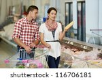 Young Family couple choosing bio food chicken meat in grocery supermarket during weekly shopping - stock photo