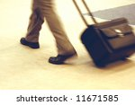 Fast walking business man (blurred legs and luggage only) pulling a small suitcase on wheels - stock photo