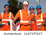 "Small photo of Elsfleth, Germany - August 29, 2018: Stephan Weil, Prime Minister of Lower Saxony together with three workers of the construciton company ""Joachim Tiesler KG"", all dressed in orange working suit"