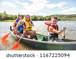family in a canoe on a lake... | Shutterstock . vector #1167225094