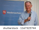 "Small photo of Elsfleth, Germany - August 29, 2018: Portrait of Stephan Weil, Prime Minister of Lower Saxony with microphone in his hand in front of blue background with the word ""Niedersachsen"" and coat of arms"