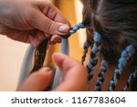 hairdresser weaves braids with... | Shutterstock . vector #1167783604