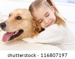 Stock photo cute little girl hugging golden retriever with love eyes closed smiling 116807197