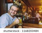 happy handsome man holding beer ... | Shutterstock . vector #1168203484