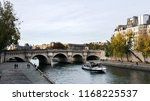 """Small photo of Paris, France - November 01, 2017: Autumn embankment of the river Seine. Large walking tourist boat. Boats tied up on Seine River. View on the Ile de la Cite """"Island of Paris"""" and Pont Neuf"""