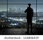businessman with phone looks in night city - stock photo