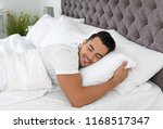 young man sleeping in bed with... | Shutterstock . vector #1168517347