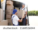male movers unloading boxes... | Shutterstock . vector #1168526044